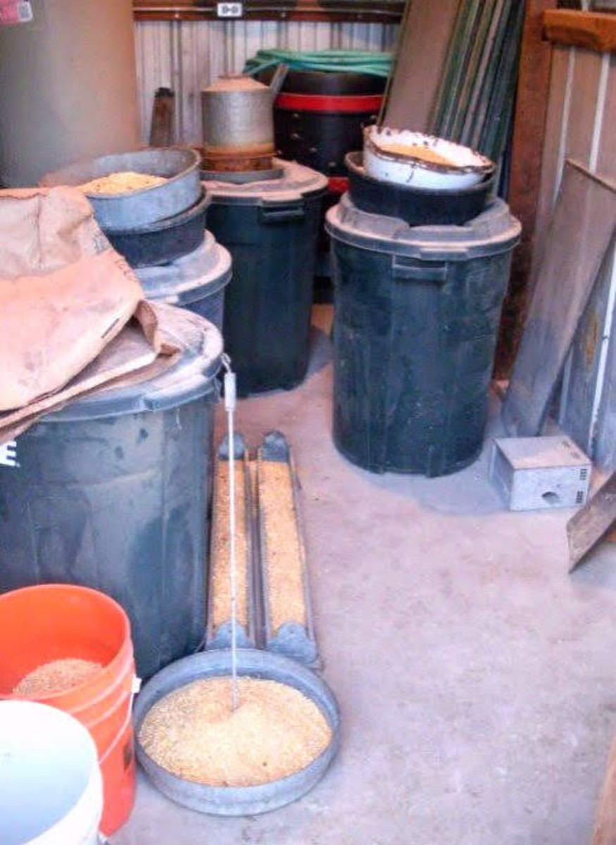 The front room of the chicken house is full of barrels of grains and feed pans.