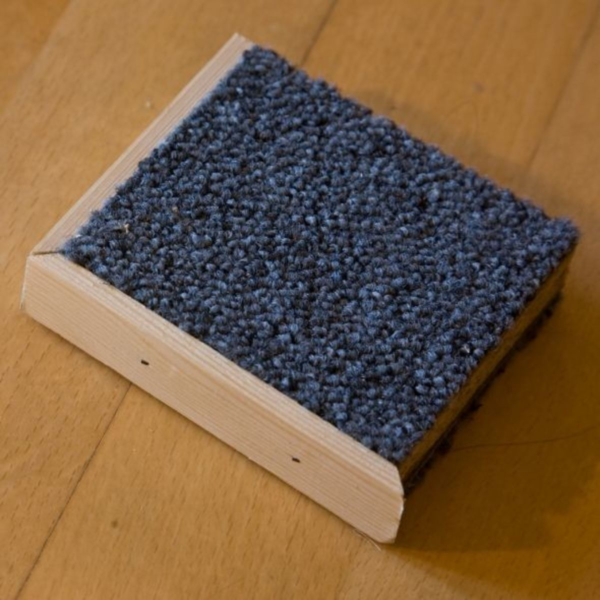 Scrap wood covered in carpet (with trim on edge).
