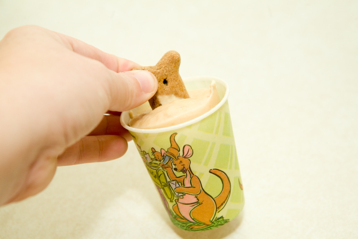 Gently squeeze the sides of the cup to release the pupsicle. You may have to also slightly push on the bottom.  Once it's released, pull it out by the biscuit handle. If you pull on the biscuit before it's released from the cup, the biscuit may break