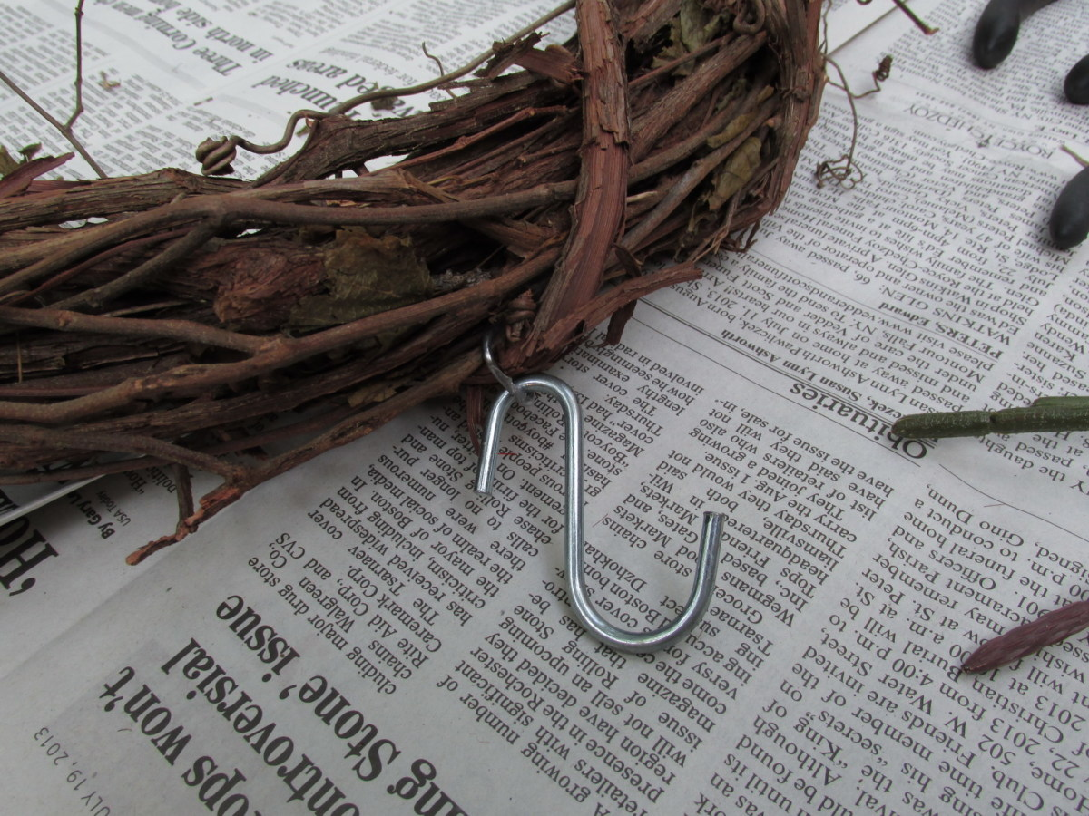 Metal hook that came already inserted into the grapevine.  I could then attach my 'S' hook to that for easy hanging.