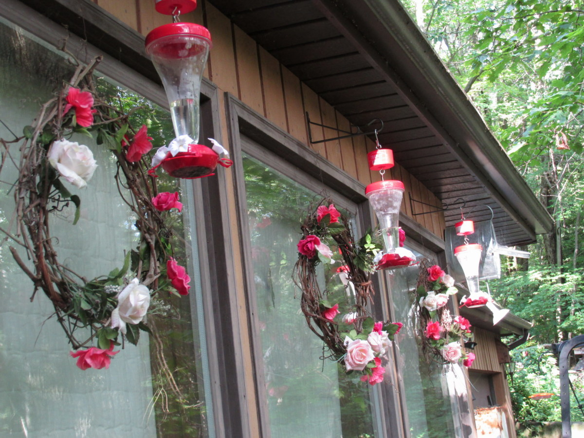 Three rose wreaths and matching hummingbird feeders—one for each of my front windows.