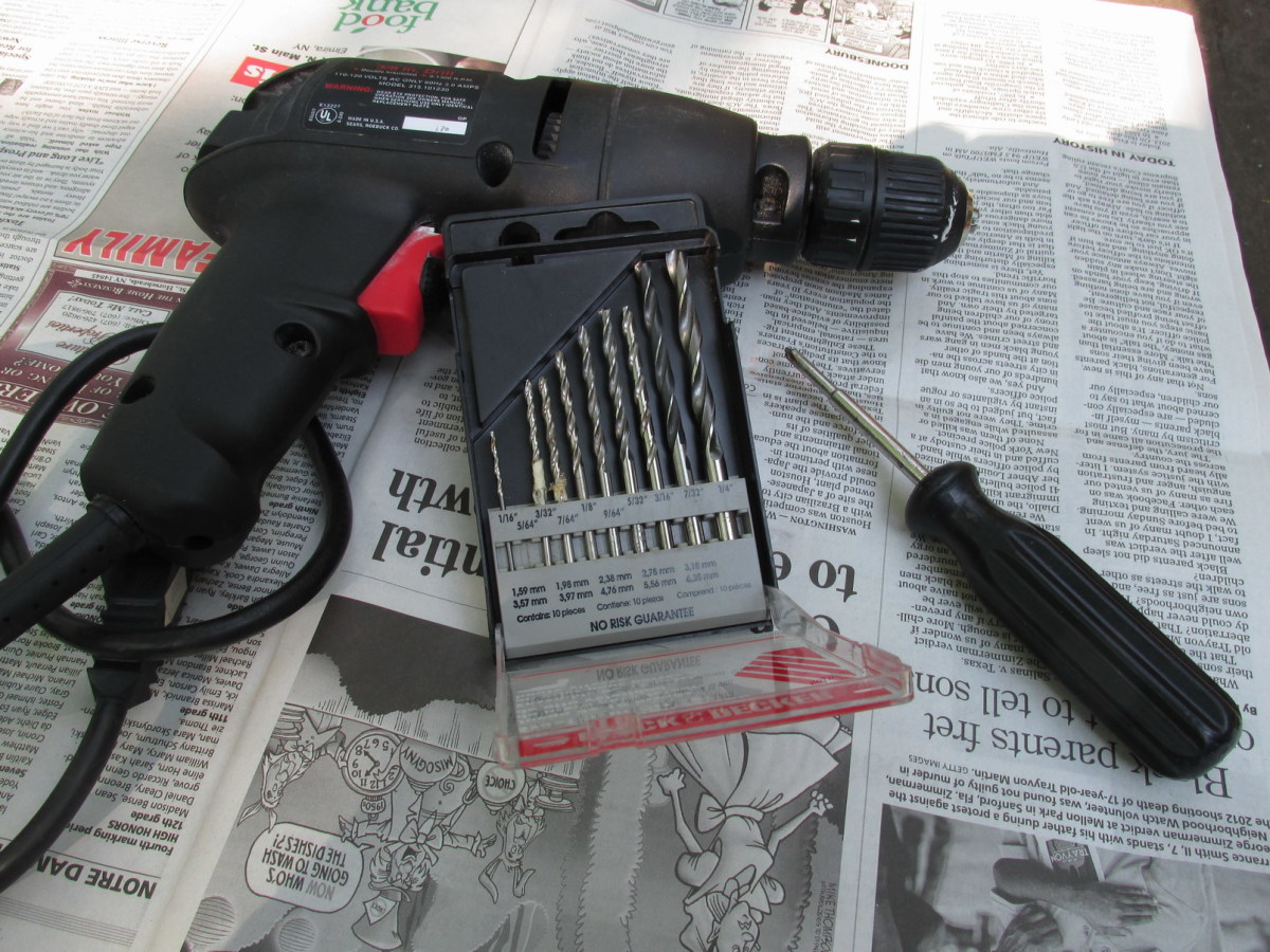 Electric drill, set of drill bits and screwdriver for attaching the scroll plant hanger.