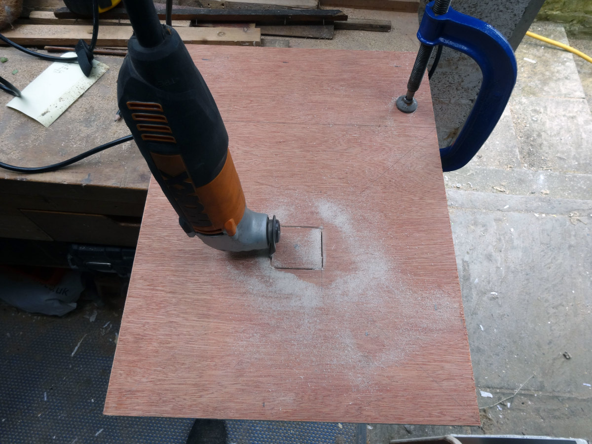 Using my SoniCrafter to cut a square hole in the plywood.