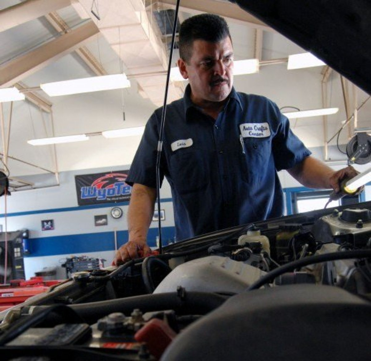 An auto mechanic prepares a vehicle for an emissions test.