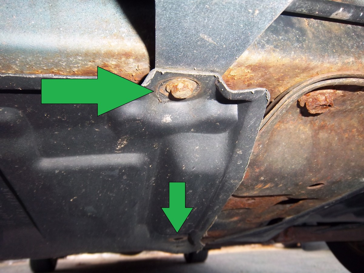 The plastic cover hiding the drain plug and oil filter is held in place by 10-mm bolts. Be careful removing them as they are likely rusty and may strip or break.