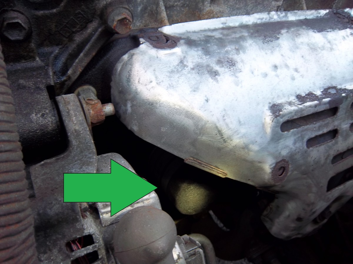 The oil filter, lurking in the shadows beneath the exhaust manifold. It's best to access it from below