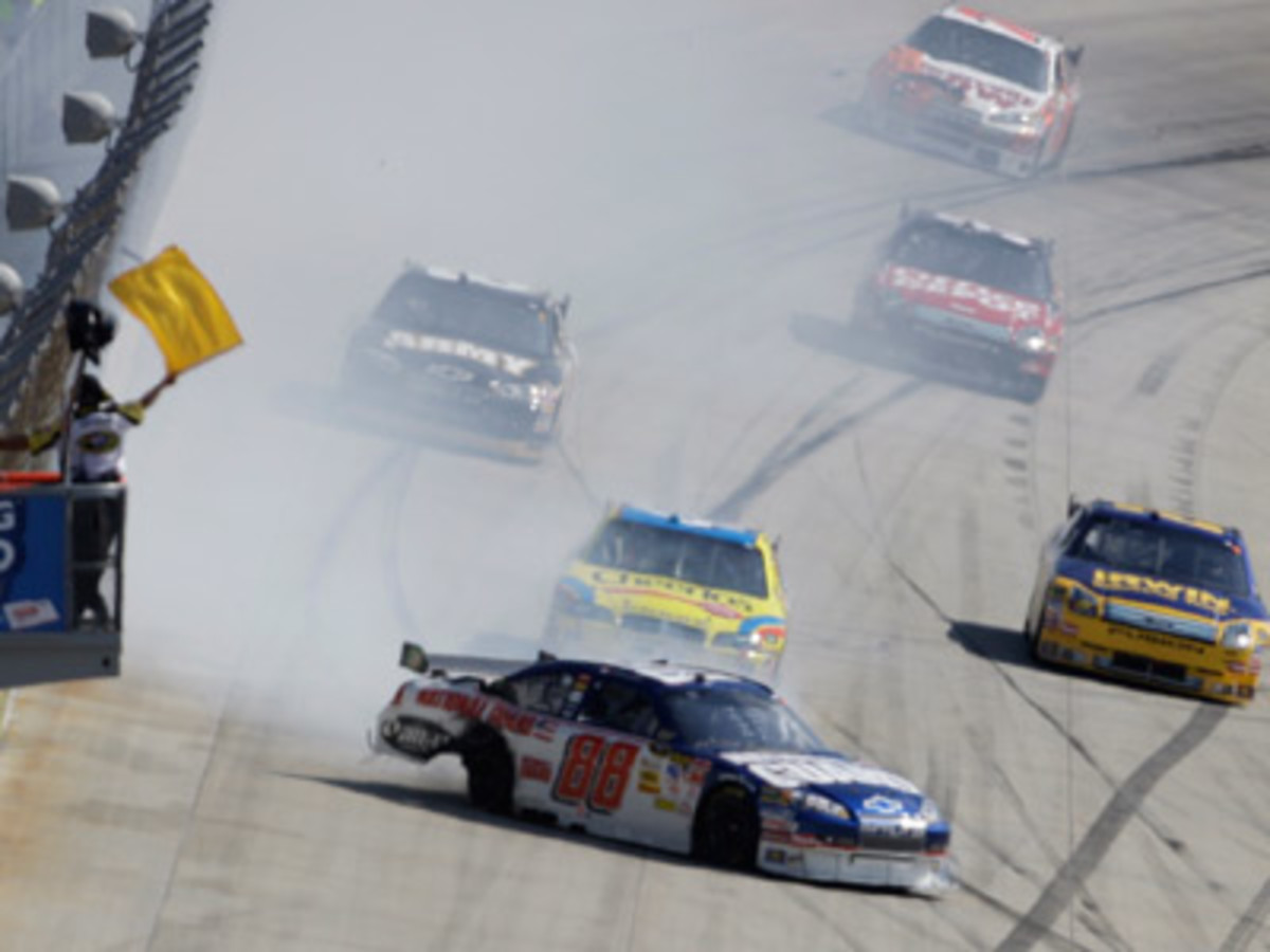 Flag man waves the yellow flag due to Dale Earnhardt Jr's car spinning across the racetrack
