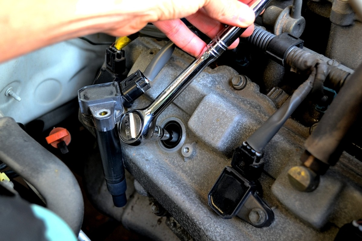 "Now with a 5"" extension bar and the 5/8"" spark plug socket, fit the socket over the plug and turn left to loosen.  Continue loosening until the plug is free, it should be stuck in the socket and easily removable."