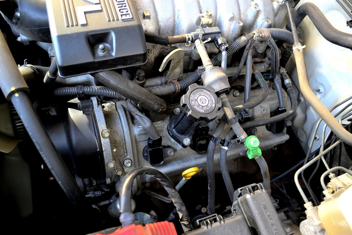 View of the driver side engine block, 4 more black cap covered plug coils.  A bit more crowded on this side with some hoses and the oil cap creating some clutter.