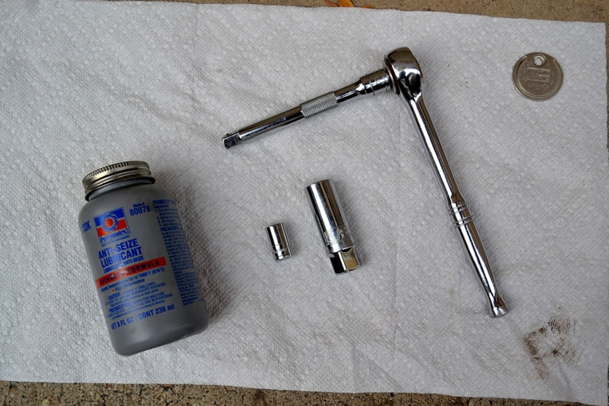 The tools, from left to right: bottle of anti-seize lubricant, a 10mm socket, a 5/8 inch spark plug socket, a 3/8 drive ratchet with a 5 inch extension bar, and a spark plug gap tool coin.