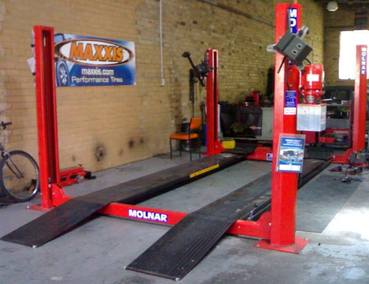 This four post vehicle hoist is a four ton with a sliding  jacking beam and wheel alignment pads.