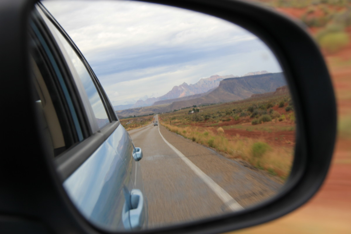 The mirror should show the side of the car and the road behind you.