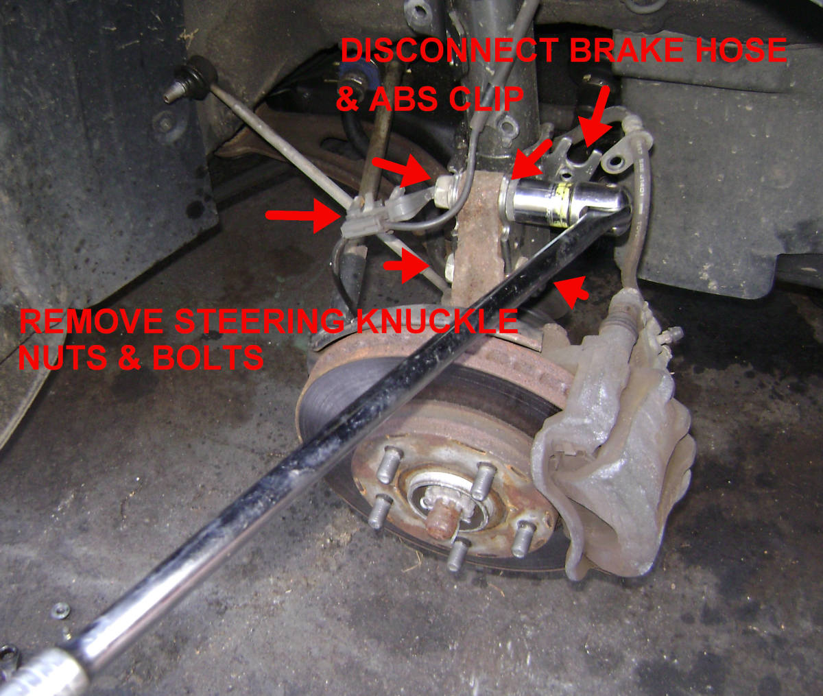 Removing the strut-to-steering knuckle bolts, brake line bolt, and ABS clip.