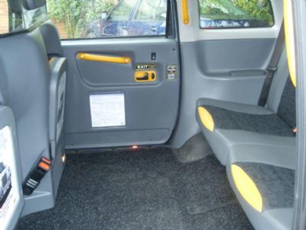 interior of TX4 taxi showing rear seats, tip-up seat, grab rail, carpet