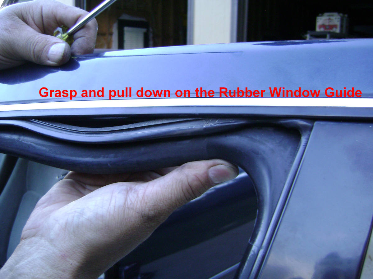 g. Grasp the rubber window guide and pull it down.