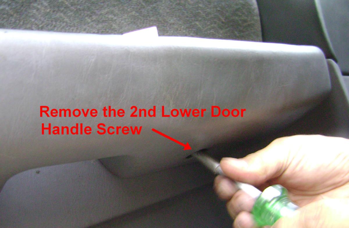 h. Remove the lower door handle screw.