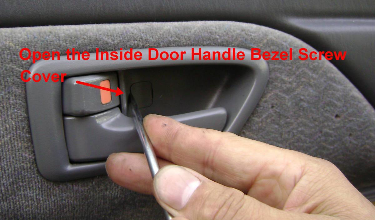 Open the inside door handle bezel screw cover for 1995 toyota camry window regulator