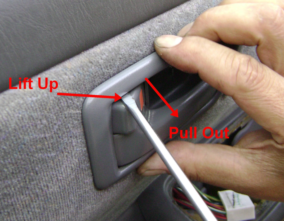 e. Position a thin screwdriver between the handle bezel and the inside handle (see photo) and release the upper connection by pulling out.