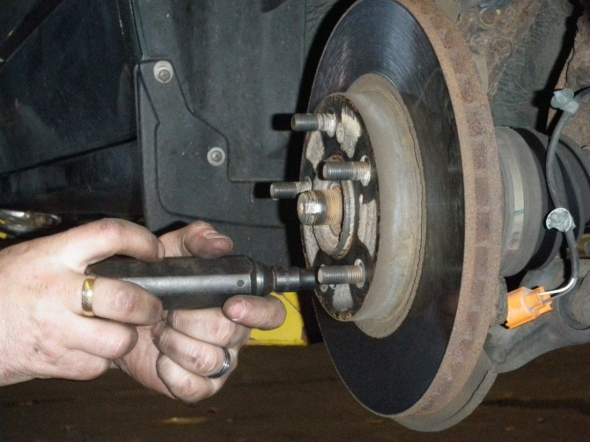 Removing rotor screws with an impact driver and remove rotor and caliper assembly.