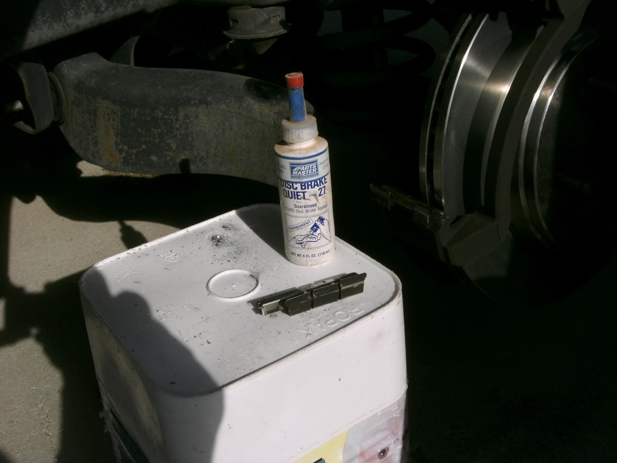 Commercial product to quieten brake squeal when changing brake pads.  The clips holding the caliper assembly in place are also shown.
