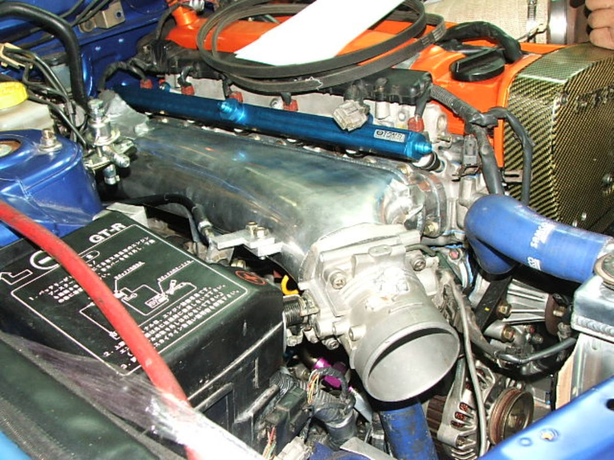 A NOZZS RB series intake manifold fitted to an RB26.  The water outlet pipe clears the manifold.  For those running larger batteries, you may require a battery relocation or a smaller battery.