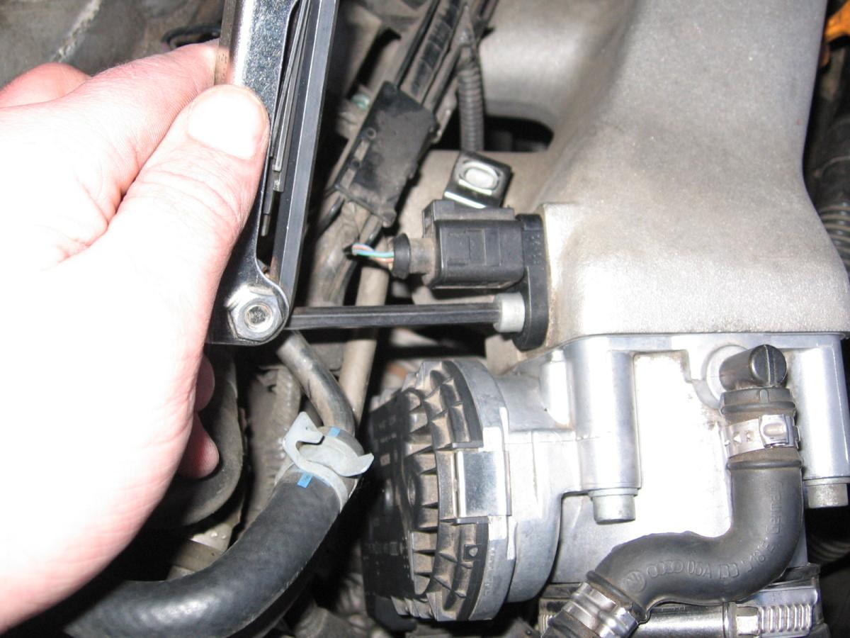 Unscrewing the bolt holding the IAT sensor