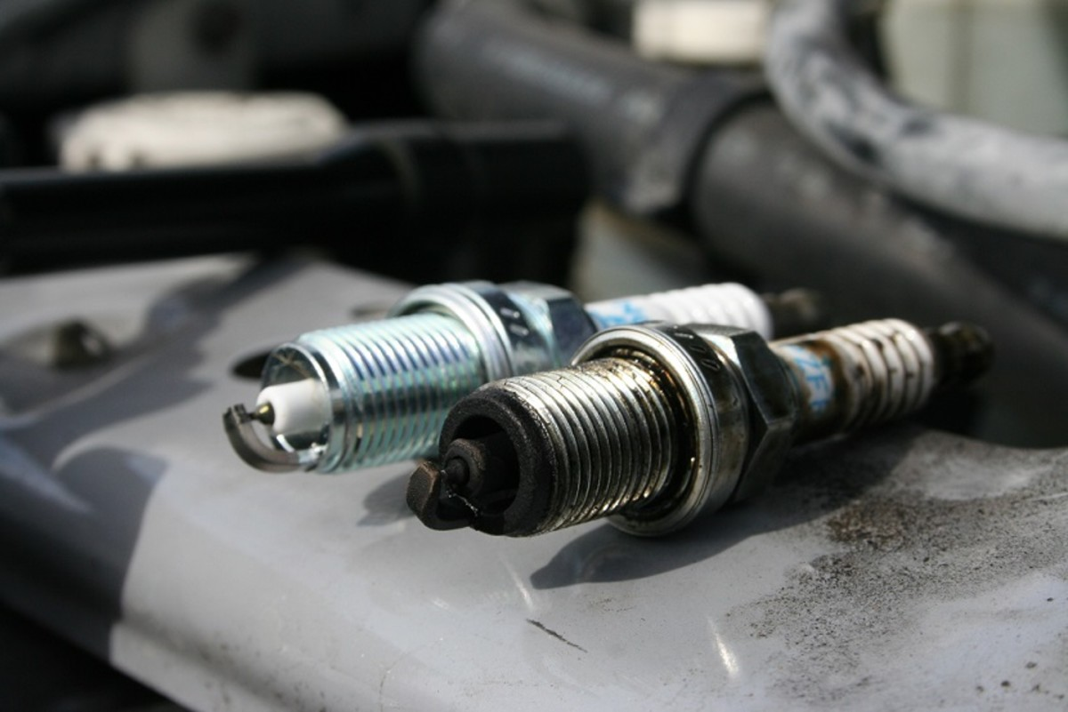 A new spark plug versus an old spark plug. Replace your plugs about every 100,000 miles to keep your vehicle running smooth.