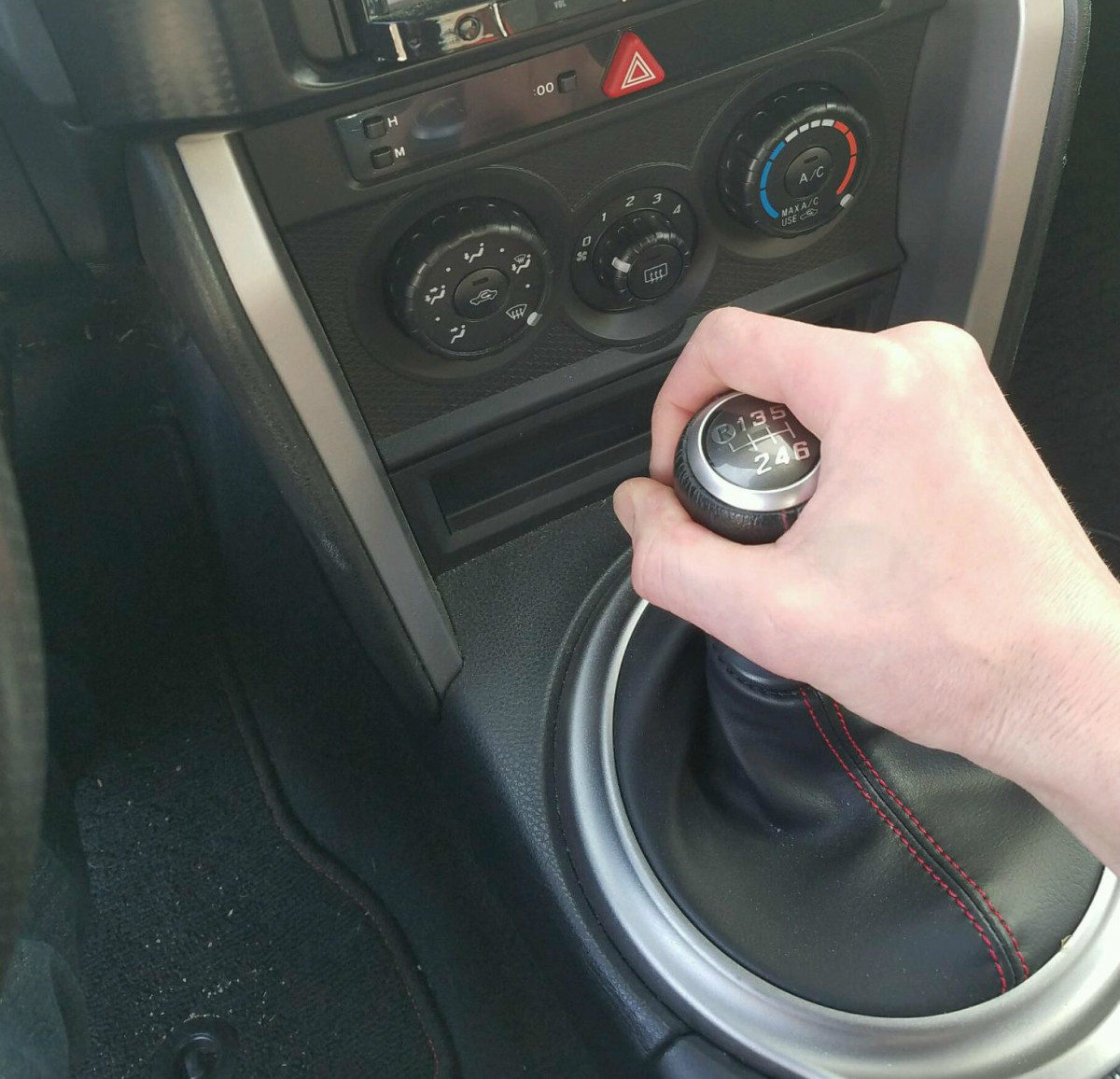 Press the clutch in all the way and move the gear shift into first gear. Usually this is to the left and up away from you.