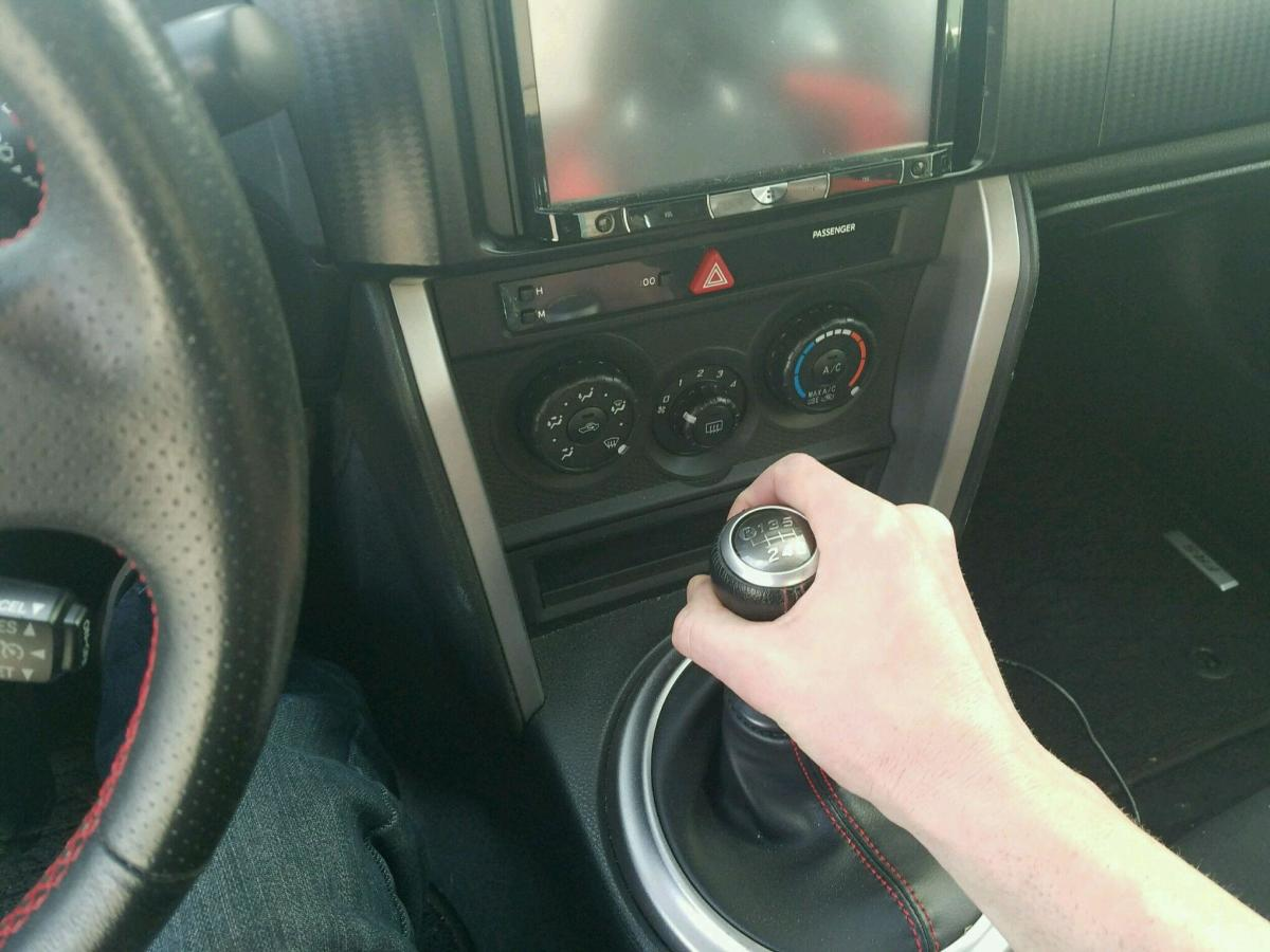 To shift from first to second, press in on the clutch and pull the gear shift down (towards you). To shift up to third gear, press in on the clutch and move the gear shift up and to the right.