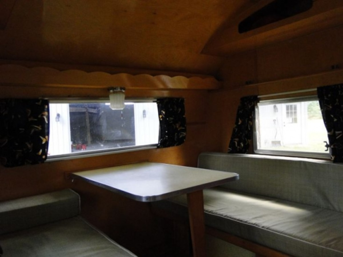 The lovely convertible dinette - bed. Dinner and dominos for 4-6. Dinette folds down to sleeps 2 adults, one dog, a toddler and 2 kids could go above in the original canvas bunks... if you're not the claustrophobic type.
