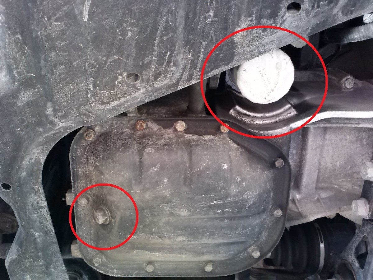 In the lower left, we see the oil drain bolt which requires a 14 mm socket to remove and in the upper right of this photo, we see the oil filter which can generally be removed by hand without any additional tools.