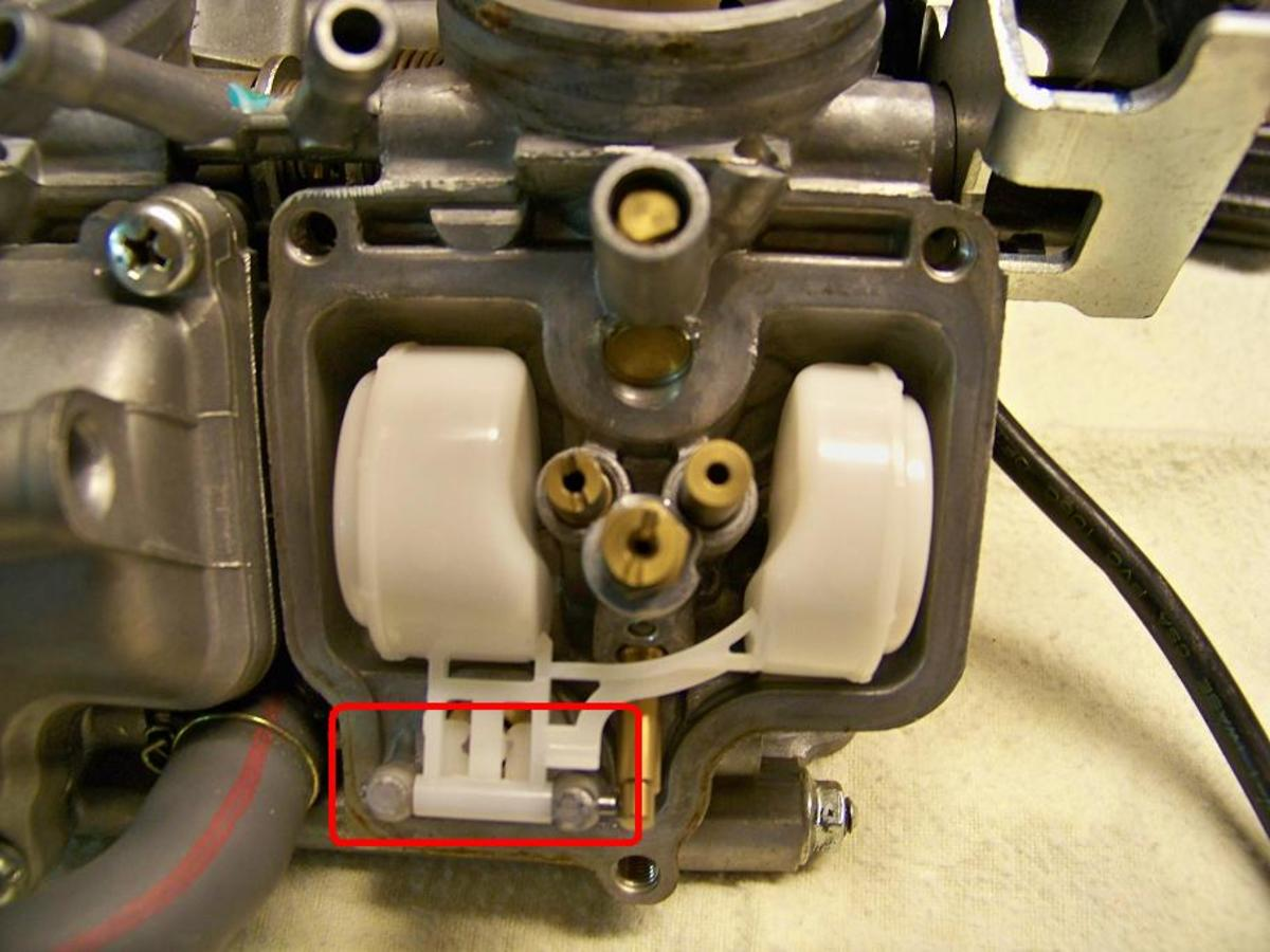 Remove the pin that holds the float in place (circled in red). Remove float and float valve.