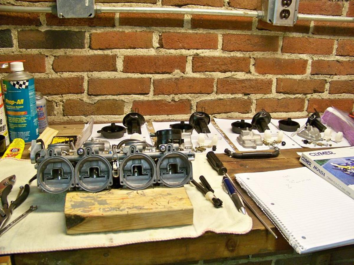 Picture of carburetors completely disassembled and ready to be cleaned. Note that all of the parts in background neatly organized on notebook paper.
