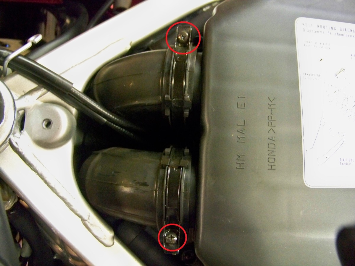 Loosen screws on air duct clamps (circled in red), disconnect air duct hoses from the air cleaner cover.