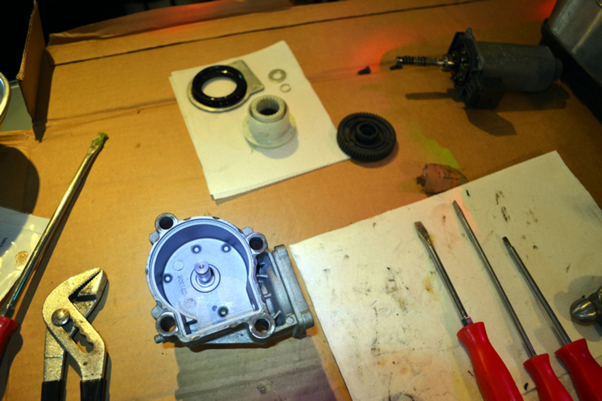 BMW transfer case actuator motor disassembled (brand new black replacement gear pictured).