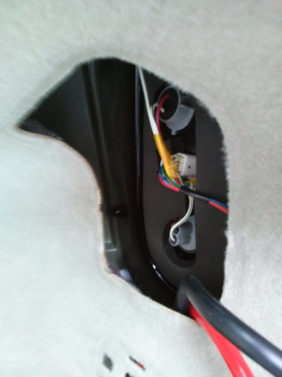 Route both the positive and negative power cables through the right rear taillight access hole.