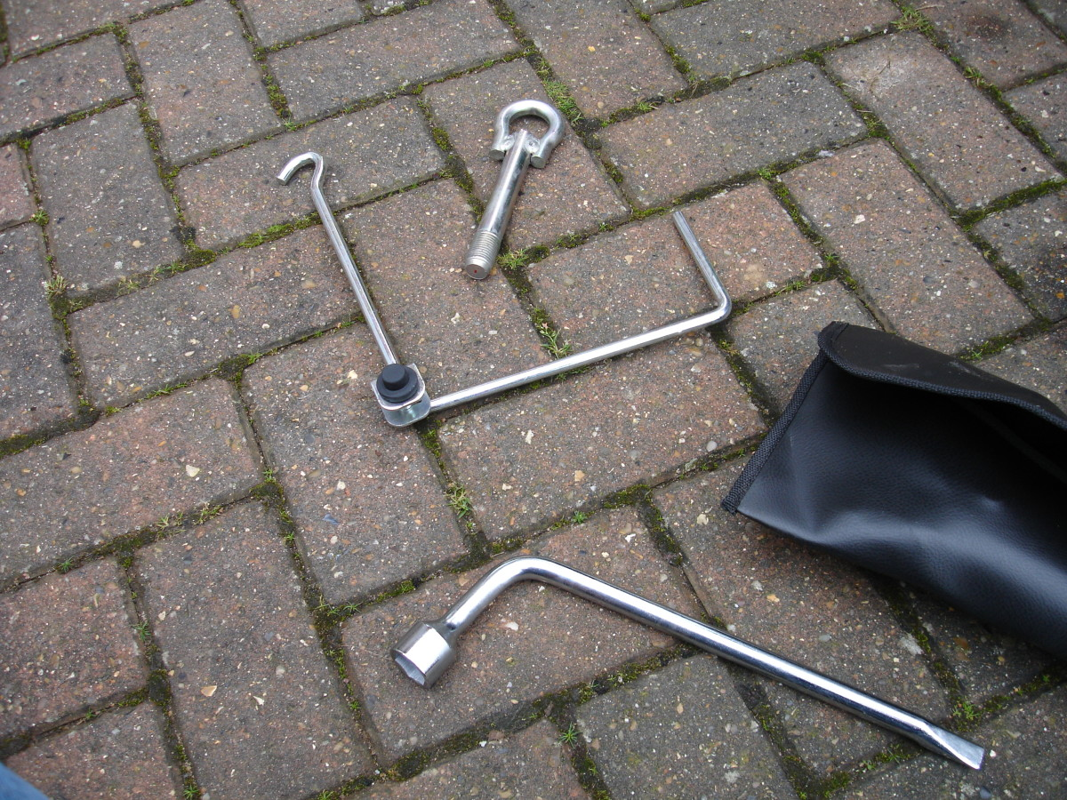 Tyre tools - spanner, jack handle and... tow bar thing.