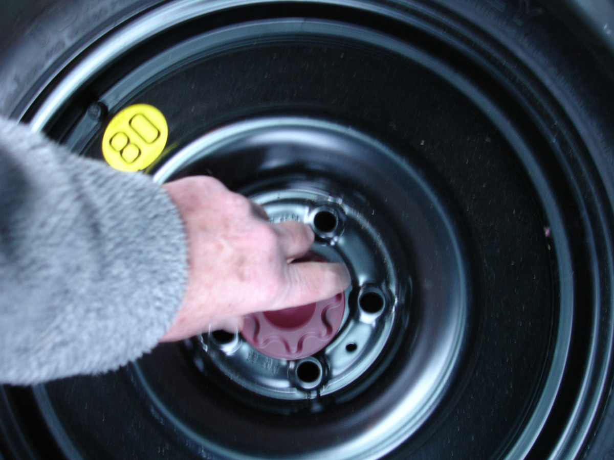 Unscrewing the spare tyre retainer