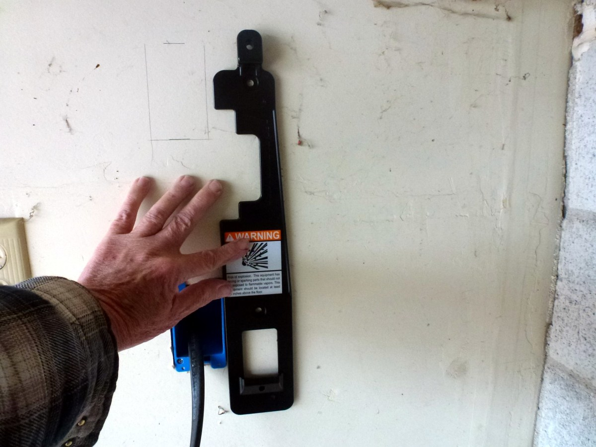 Holding the mounting bracket to the wall to mark the holes for drywall anchors.  A level was used to assure it was vertical.