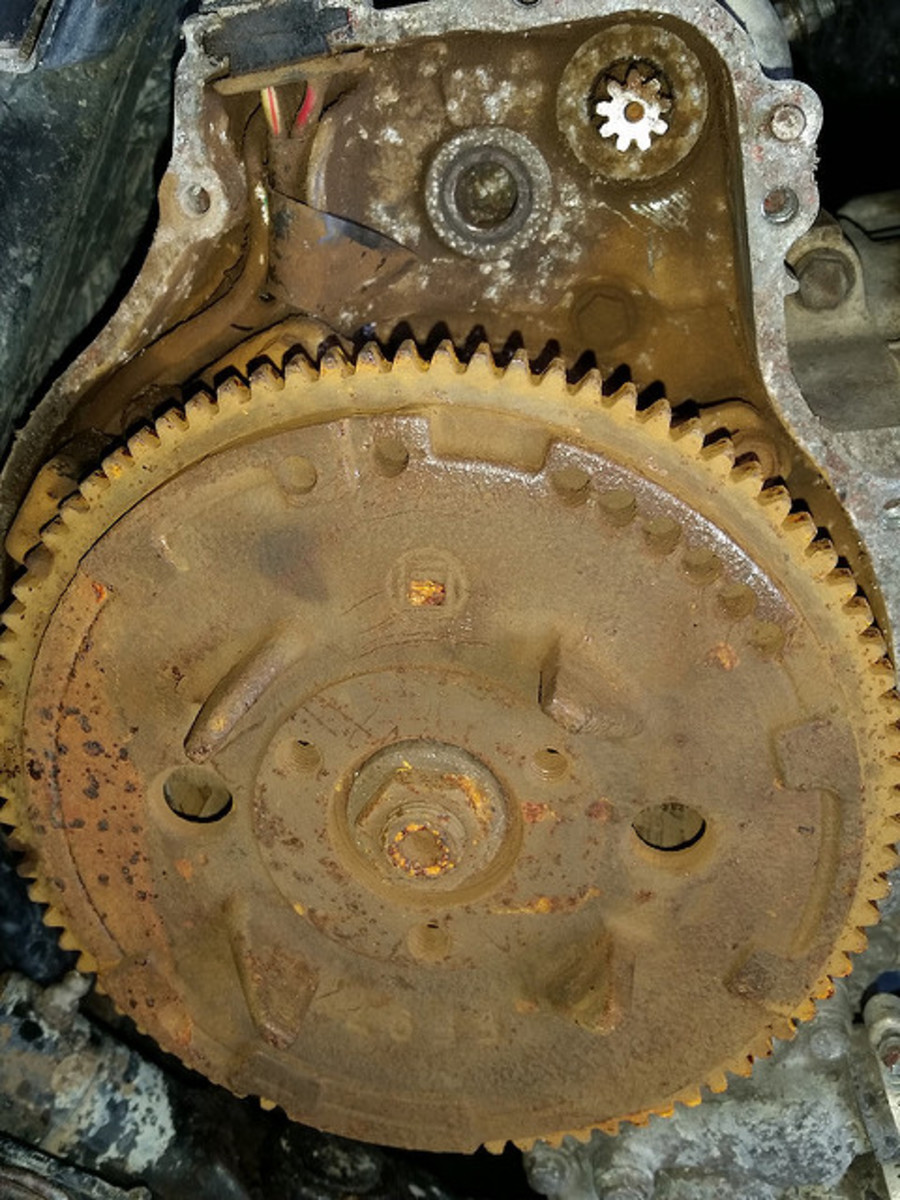 The starter motor pinion gear meshes with the flywheel on the back of the engine.