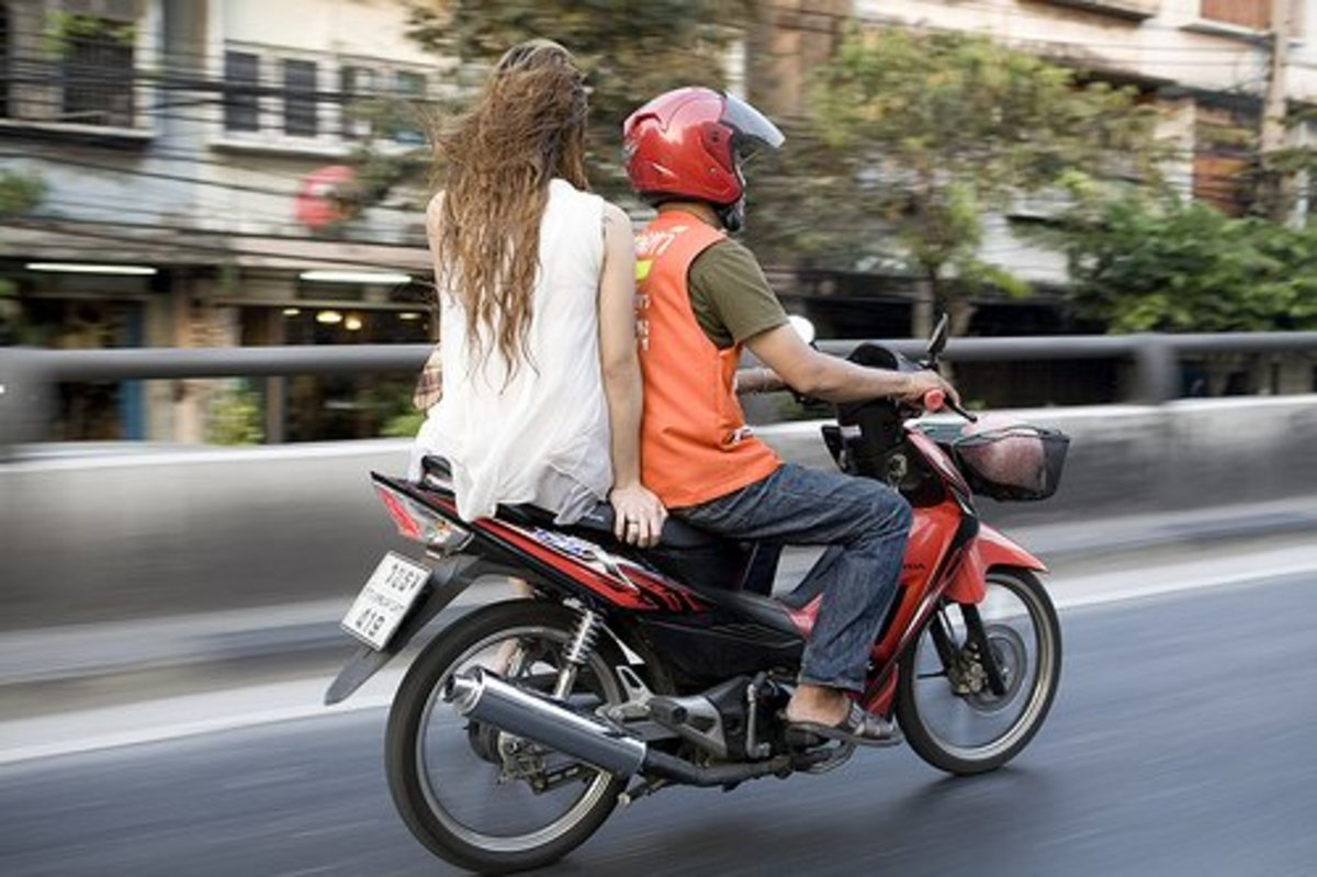 You can recognize bike-taxi drivers by their orange vests.