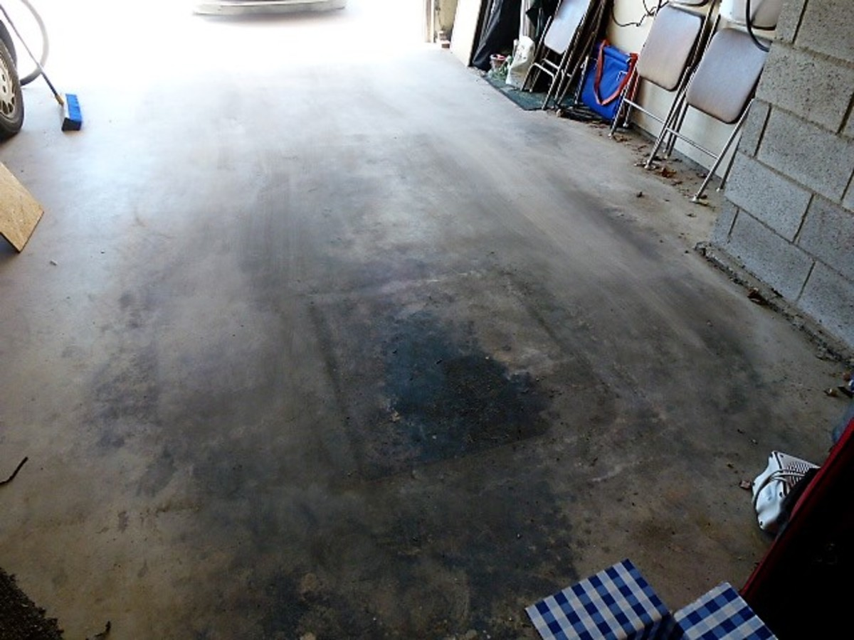 This garage floor has a large oil spot that was covered with scrap plywood before laying the awning down.  Don't set your new awning in a puddle of oil!