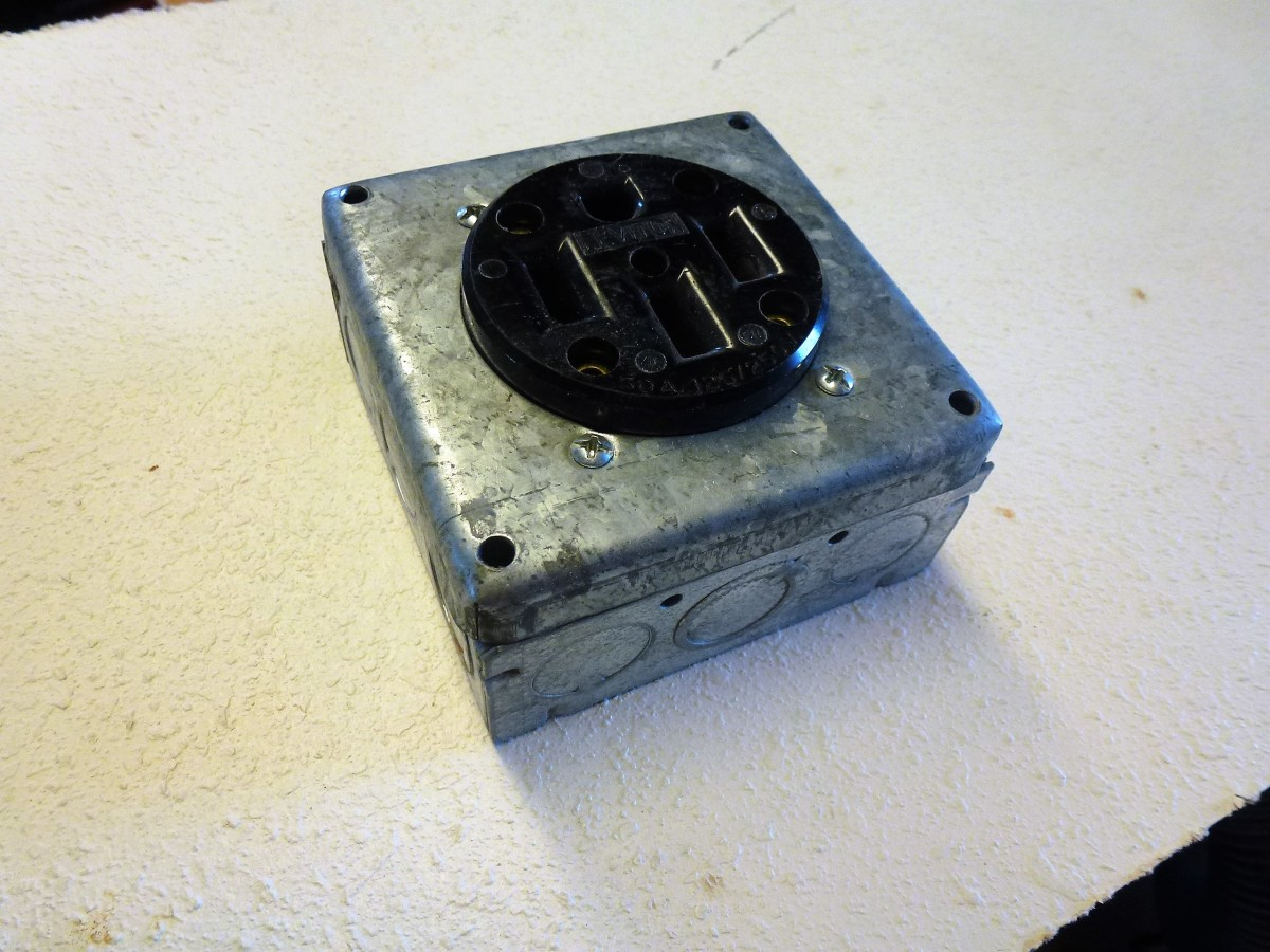 An indoor, two gang box with a mounting plate and outlet mounted to it.