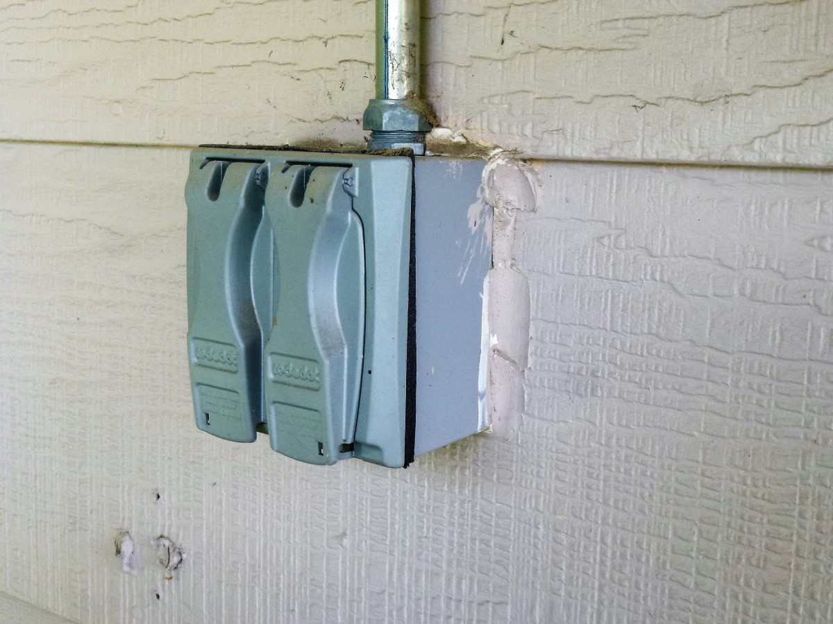 A double gang box surface mounted on wood siding.  Not an RV outlet - it has a light switch and a 20 amp outlet inside.