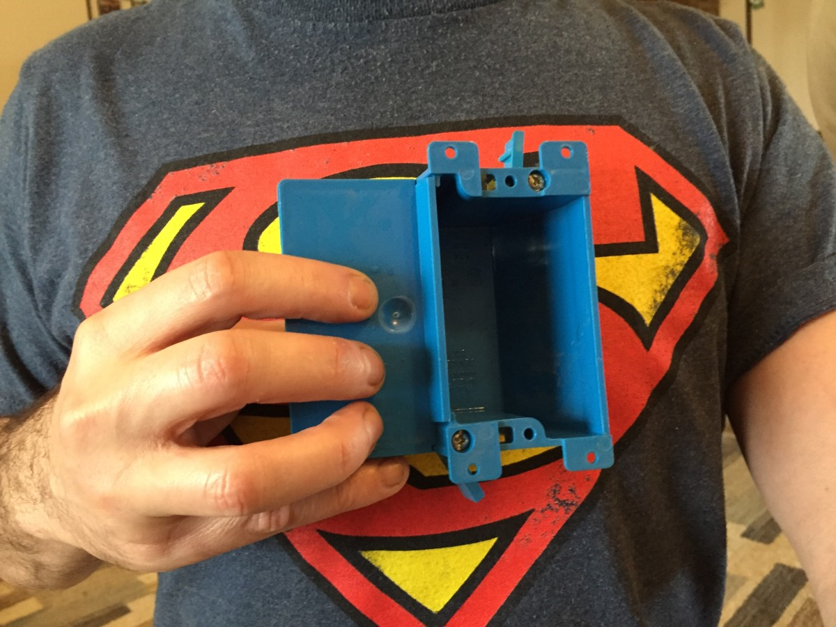 Superman and a Carlon B117RSW Work Outlet Box, one gang, 3.64-inch length by 4.07-inch width by 2-inch depth.