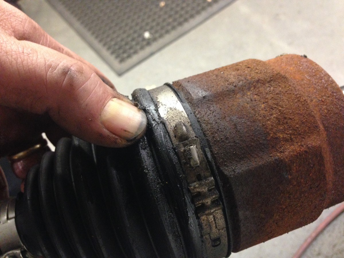 Here you see an inner CV joint boot split near the cup, causing grease to leak from the joint.