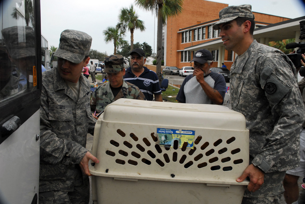 A U.S. airman and a soldier carry a pet carrier onto a bus at Ball High School in Galveston, Texas, during evacuation from the area following Hurricane Ike on Sept. 14, 2008.