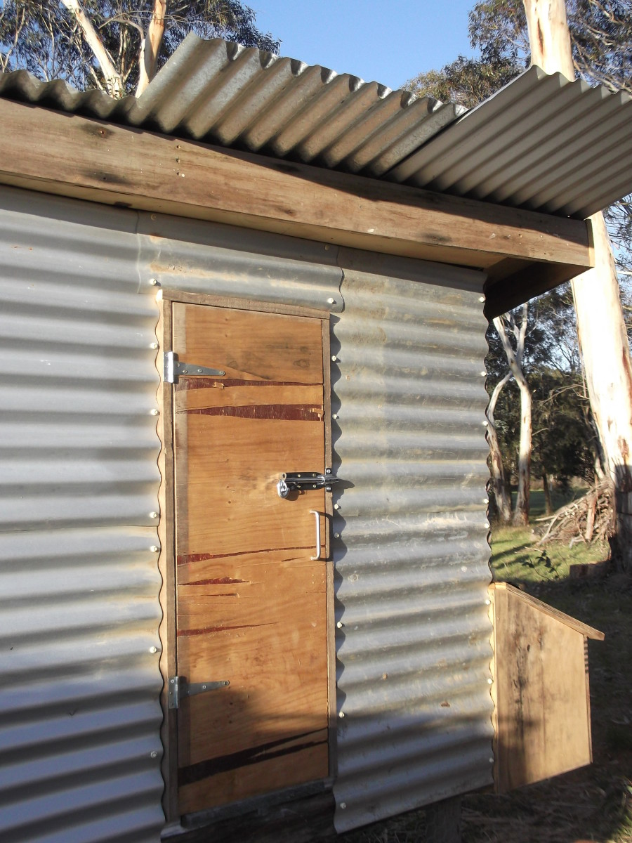 If we need access to the inside of the chicken house, we don't have to enter the chicken run. Recycled wood for door and laying boxes needs painting. The roofing iron yet to be finished.