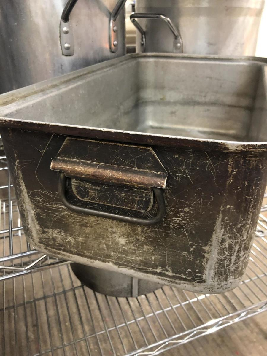 The vintage pan is shown in it's original place, in a commercial kitchen rack.