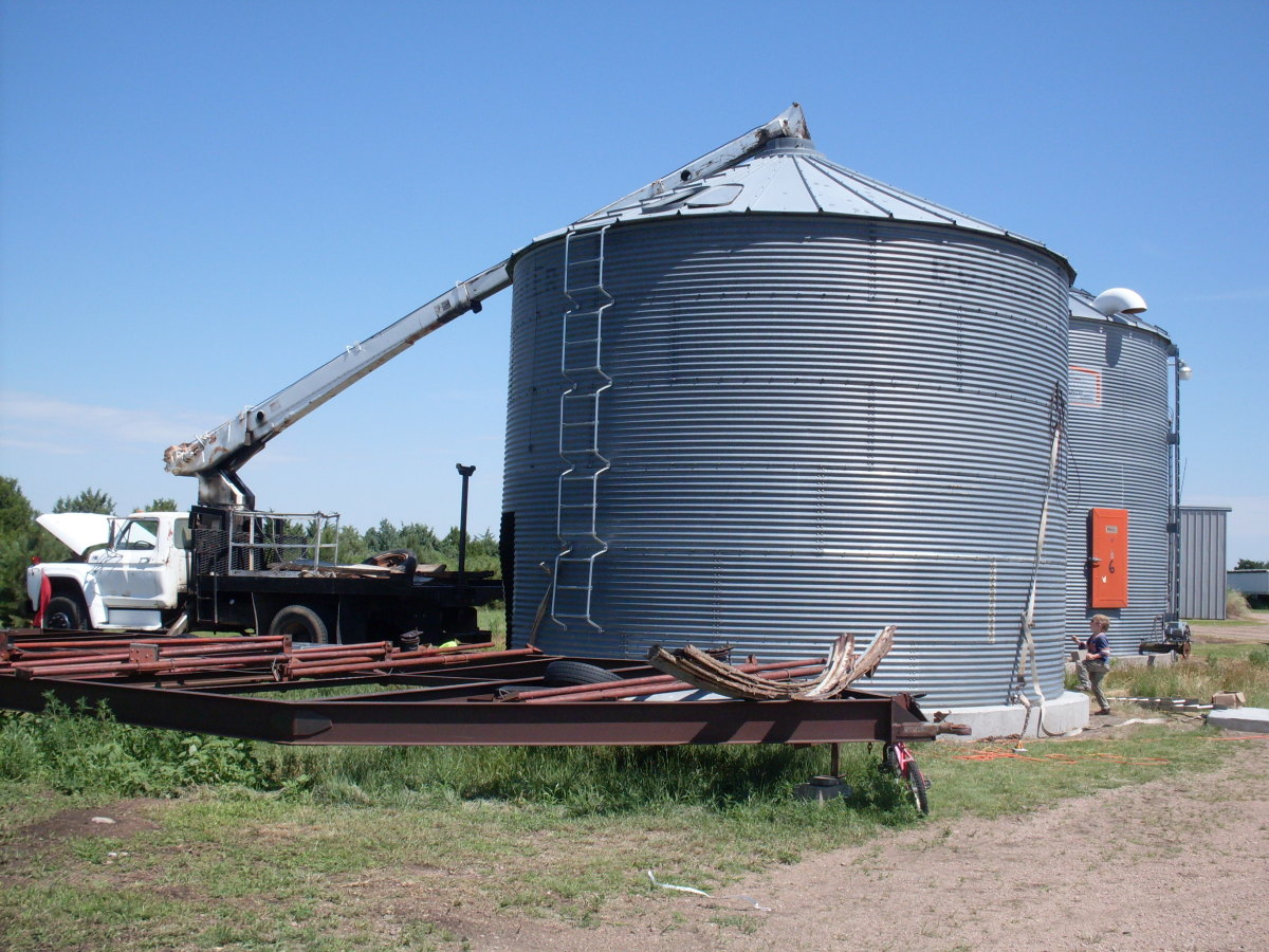 A nearly completed bin. This one lacks a ring of sheets, and is being held down by the boomtruck, as it's not anchored to the cement. Ever watched a kite take off in the wind? A grain bin will do the same thing.